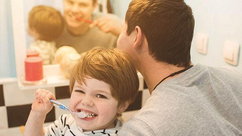 Padre E Figlio Intenti A Curare La Propria Igiene Orale Quotidiana A Casa