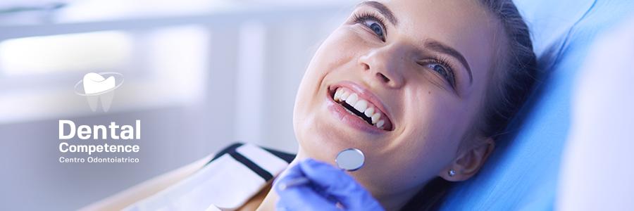 Donna sorridente durante visita odontoiatrica e logo Dental Competence Grosseto