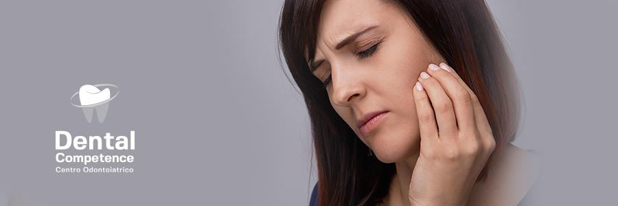 Donna con dolore dentale e logo Dental Competence Grosseto