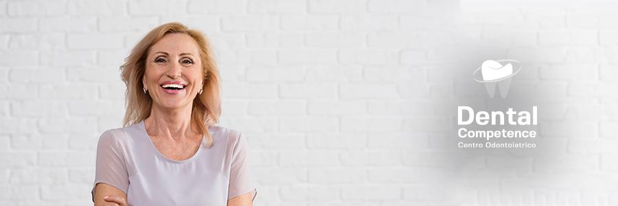 Signora sorridente con nuovo impianto dentale e logo bianco di Dental Competence Grosseto