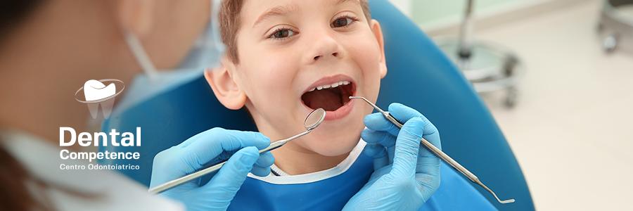 Bambino durante visita presso l'odontoiatra pediatrico e logo Dental Competence Grosseto